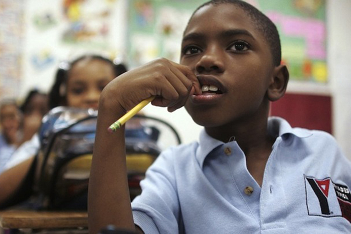 Third grade student Thaddeus Rhodes, 9, sits in class. Photo by Mario Tama/Getty Images