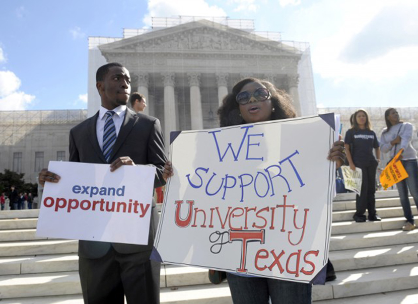 Jheanelle Wilkins of New Castle, Del., right, and Neo Moneri of Beltsville, Md., participate in a rally outside the Supreme Court.