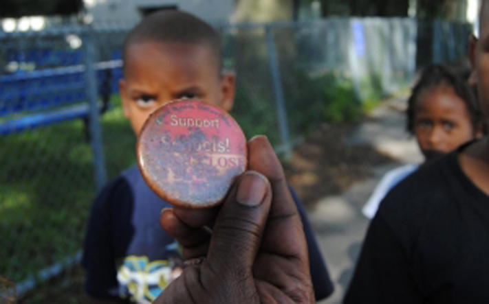 Irene Robinson holds a protest button denouncing the school closures of the 2013