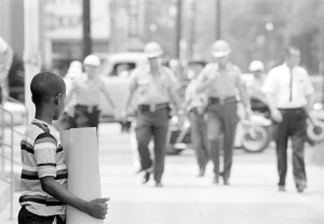 A brave young boy at Dallas County courthouse in Selma on July 8, 1964. Selma sheriff deputies approach and arrest him. Photo used by permission of  Matt Herron/Take Stock Photos