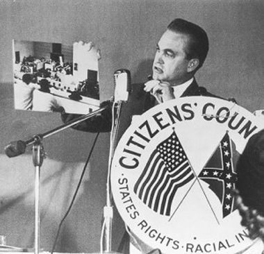 "Alabama Governor George Wallace, holding photograph of ""agitators"""